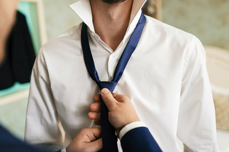 Grooms friend helps to fix a blue tie on grooms neck while they stand in the room