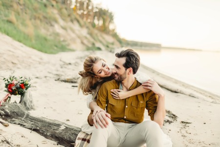 A young couple is smiling and hugging on the beach. Beautiful girl embrace her boyfriend from back. Wedding walk. Artwork Stock Photo