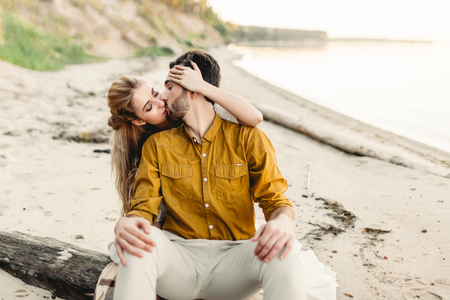 A lovers is kissing. Young couple is having fun and hugging on the beach. Beautiful girl embrace her boyfriend from back. Wedding walk. A newlyweds looks at each other. Artwork Stock Photo