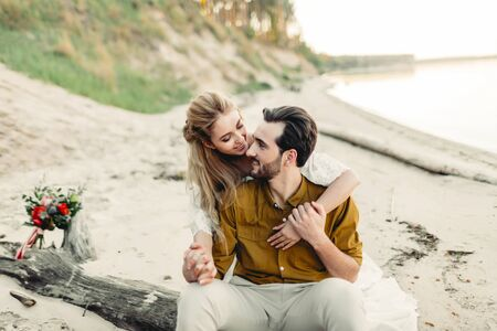 A young couple is smiling and hugging on the beach. Rustic wedding ceremony outdoors. Bride and groom look at each other with tenderness and love. Artwork. Outdoors