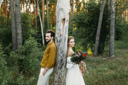 Bride and groom lean on the tree from different sides. Newlyweds are walking in the forest. Artwork