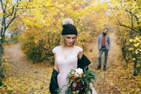 Beautiful bride in a knitted hat with a pompon are posing in autumn forest on blurred grooms background. Wedding ceremony outdoors. Standard-Bild