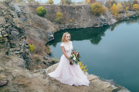 rastas: Stylish bride with a rustic bouquet is posing before a lake on the hill. Autumn wedding ceremony outdoors. Full length