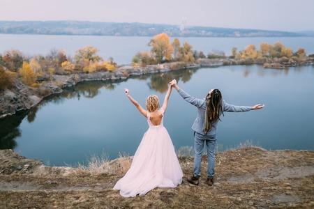 rastas: La opinión trasera los recienes casados ??elegantes de la pareja con las manos está presentando antes de un lago en la colina. Ceremonia de la boda de otoño al aire libre. Longitud total