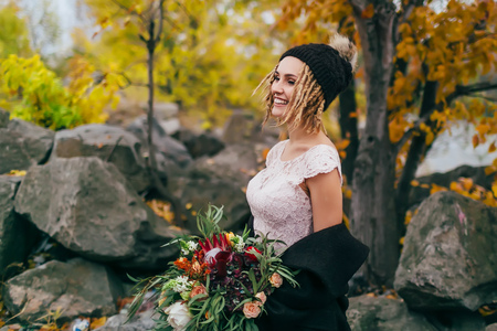 Stylish bride with a rustic bouquet is posing before a lake on the hill. Young blonde in a knitted hat with pompom and with dreadlocks. Autumn wedding ceremony outdoors. Stock Photo