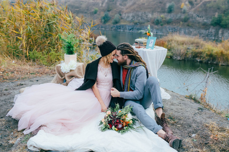 rastas: Attractive couple newlyweds laugh and smile happy and joyful moment. Autumn wedding ceremony outdoors. Stylish bride and groom with dreadlocks look at each other standing before a lake