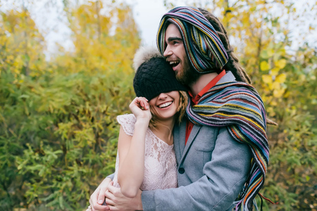 Bride in a knitted hat with a pom pom, hat covering her eyes. Groom in a colorful scarf. Wedding ceremony outdoors. Stock Photo