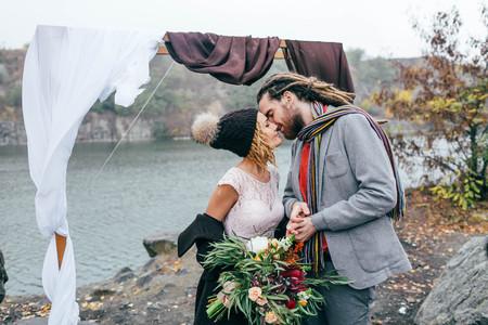 Attraktive Paare , die Lachen und lächeln glücklich und freudige Moment . Herbst Hochzeitszeremonie draußen . Stilvolle Braut und Bräutigam mit umarmen sich vor einem Meer , der zu Hause läuft Standard-Bild