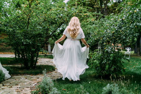 back alley: Gorgeous blonde bride in white dress is walking in the green garden. Back view. Artwork.