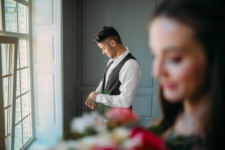 Handsome groom is preparing for wedding day on a background of blurred bride with a bouquet. Man in the festive clothes near a panoramic window. Artwork Stock Photo