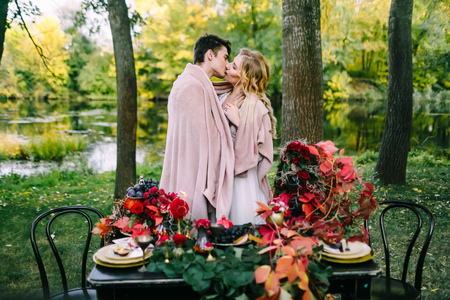 Newlyweds kissing under the plaid next to the festive table. Bride and groom in the park. Autumn wedding. Artwork