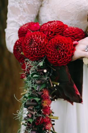 arm bouquet: Bouquet with bordeaux dahlias on bride hand. Wedding decoration.