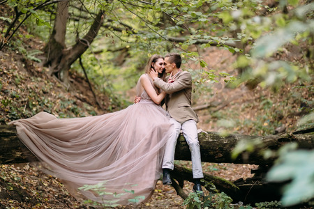 Stylish couple are relaxing on a plaid and sitting on the log. Bride and groom with dreadlocks are posing on nature.