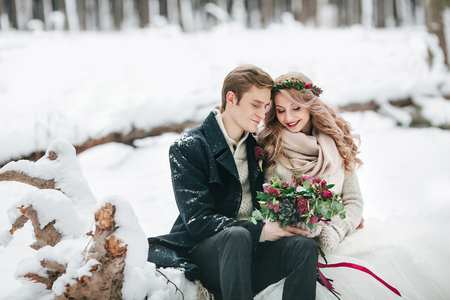 Couple in love with a bouquet are sitting on the log on background of the snowy forest. Winter wedding. Artwork Stock Photo
