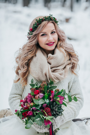 Beautiful smiling girl of Slavic appearance with a wreath of wildflowers holds a bouquet in winter background.