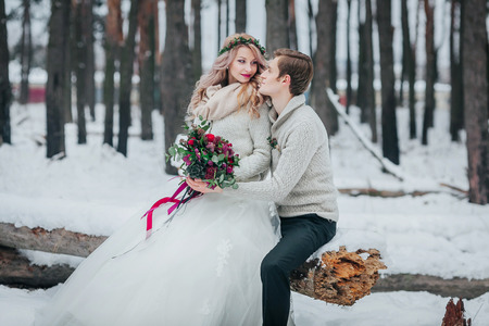 Bride and groom with a bouquet are posing in snowy forest. Winter wedding. Artwork Stock Photo