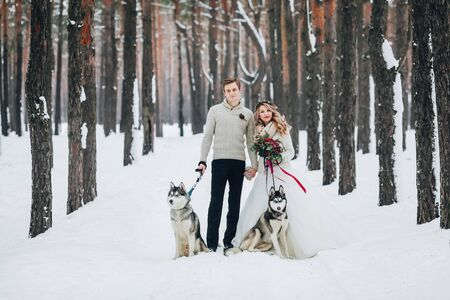 Beautiful newlyweds with two siberian husky are posed on background of snowy forest. Artwork. Copy space