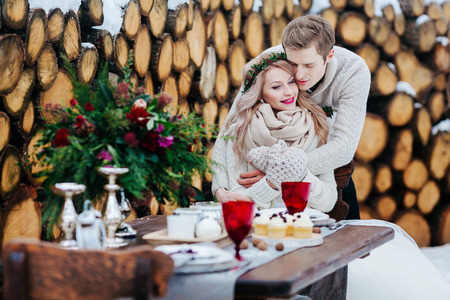 Groom is tenderly hugs his bride from the back on background of winter wedding decoration