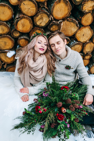 Big rustic bouquet with juniper and different flowers. Newlyweds sits on snow on the wooden background. Winter wedding