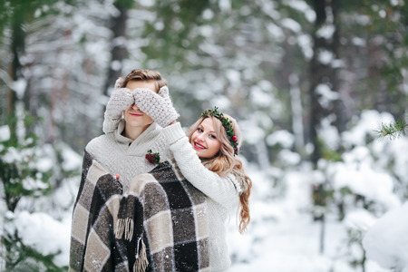 Cute girl covering boyfriends eyes by her knitted mittes. Winter wedding. Artwork. Copy space