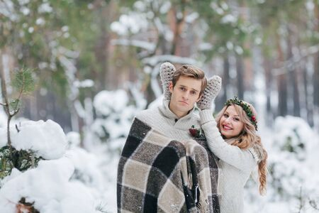 Cute girl covering boyfriends eyes by her knitted mittes. Winter wedding. Artwork. Stock Photo