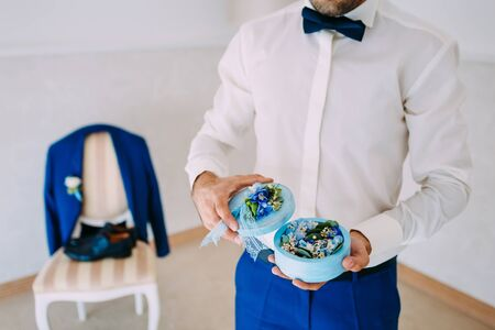 Groom holds a round box with Wedding rings with blue flowers. Artwork. Soft focus