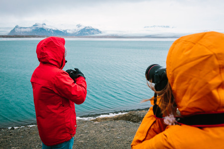Tourists taking photographs of river in the Jokulsarlon glacier lagoon in Iceland - Stock Image