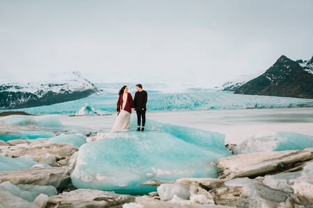 Newlyweds stand together on blue iceberg. Iceland Wedding in Glacier Lagoon.. Copy space