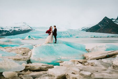 Iceland Ice Beach Or Jokulsarlon Iceberg Beach - Bride and Groom is standing on Iceberg . Copy space