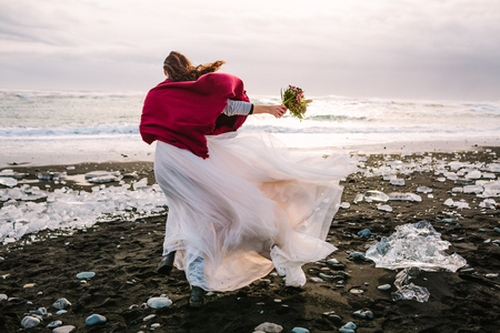 Bride in white flattering dress with burgundi plaid walking in windy day on Black Sand Beach, Iceland. Artwork. Her hair shakes by wind