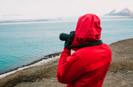 Nature travel photographer, person in red jacket taking photo of river in Iceland. Copy space 스톡 콘텐츠