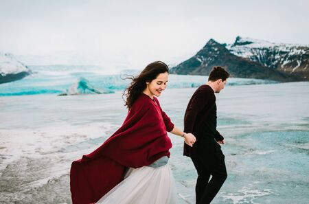 Newlyweds Are Holding Hands And Walking in Glacier Lagoon. Wedding in Iceland