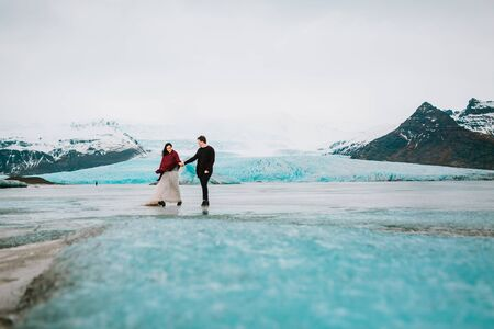 Happy Bride and Groom Are Holding Hands And Walking in Glacier Lagoon. Wedding in Iceland