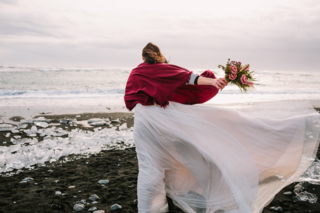 Bride in white flattering dress with a bouquet walking in windy day on Black Sand Beach, Iceland. Artwork. Her hair shakes by wind 스톡 콘텐츠