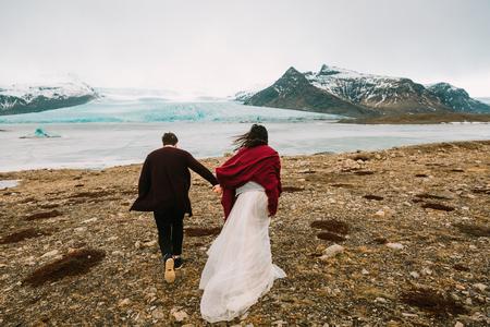 Bride and groom runs together. Iceland Wedding in Glacier Lagoon. Rear view. Artwork