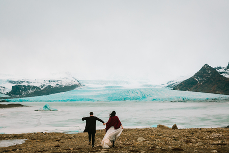 Iceland Wedding in Glacier Lagoon. Bride and groom runs together. Rear view. Copy space