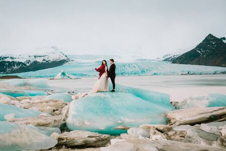 Iceland Wedding. Beautiful newlyweds stand on glacier in Glacier Lagoon in cold windy day. Copy space