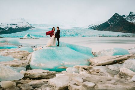 Iceland Ice Beach Or Jokulsarlon Iceberg Beach - Bride and Groom is standing on glacier. Copy space