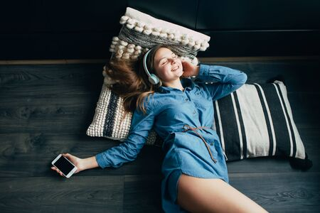 Smiling teenage girl with long hair lying at floor with pillow. Relaxing with cool music in headphone. Attractive student listening favourite songs via modern earphones using cellphone during morning