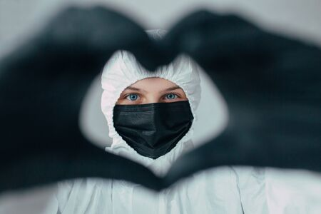a doctor in a white protective medical mask shows a heart in a black gloved hands into the camera, thinks about the consequences of the coronavirus epidemic, unity people and love each other