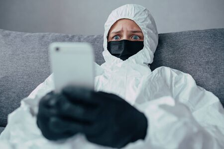 A nurse in a viral protective suit wearing, medicine mask and black gloves looks at the phone and isolated worries about the spread of coronavirus. Virologist is afraid of the coronavirus epidemic.