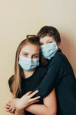 Caucasian teenagers brother and sister in a face mask hug and lovingly support each other during difficult times during self-isolation in quarantine due to the outbreak of the coronavirus epidemic. Stockfoto