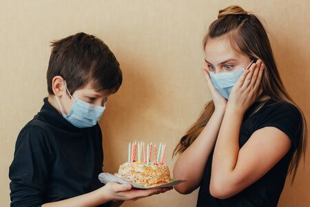 Caucasian brother wishes his sister a happy birthday and gives her a cake with candles. Isolated quarantine celebration without friends due to outbreaks of coronavirus. Supporting in difficult times. Foto de archivo