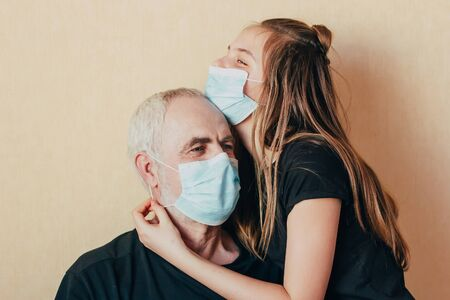 granddaughter in a face mask hugs and wants to protect grandfather from an epidemic. Family support during quarantine isolation due to outbreaks of coronavirus. Elderly risk zone.