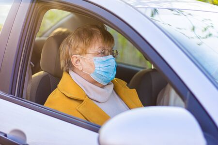 An elderly woman in a medical face mask on the passenger seat in the car. Driving to the hospital during Coronavirus pandemic concept. Road trip, travel and old people concept - happy senior couple