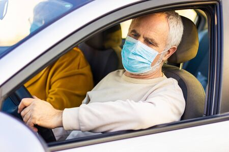 Senior man in a medical face mask driving a car. Coronavirus pandemic concept. Road trip, travel and old people concept - happy senior couple driving in car