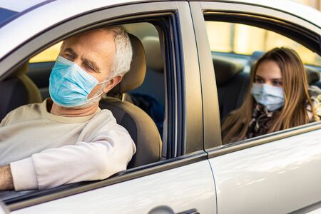 Senior man driving car with his granddaughter sitting behind and looking through window. Grandfather and granddaughter in face mask be safe in the car. Road safety. Coronavirus pandemic.