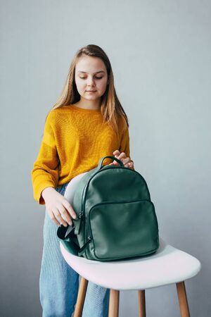 teenage girl looks on leather rucksacks and to fasten a backpack that lies on a white modern chair. Beautiful girl in yellow sweater and blue jeans stay in interior. Trendy casual outfit