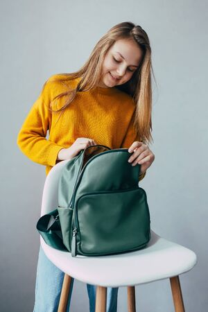 teenage girl looks inside leather rucksacks that lies on a white modern chair. Beautiful girl in yellow sweater and blue jeans stay and peek in green backpack. Trendy casual outfit