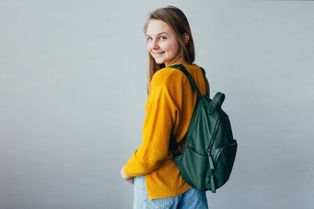 teenage girl looking at camera and smiles. Beautiful student girl standing in yellow sweater and blue jeans and green backpack dressed on shoulders. Trendy casual outfit for teen woman. hands in pock